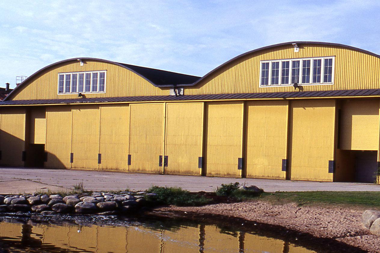 Flyghangaren sedd från vattnet. En gul byggnad alldeles intill stranden. Taket är vågformat. Hela nedre våningen är försedd med skjutdörrar. Den övre våningen har två spröjsade fönster.